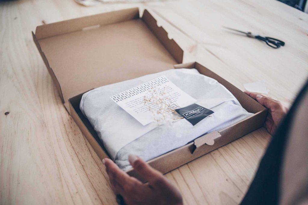 Paquetes bonitos que salen del Taller Mundaya, en caja de cartón y envueltos en papel seda.